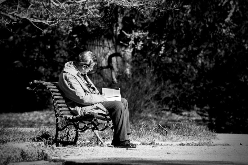 Man sitting on a park bench reading a book. It is a moody black and white scene.